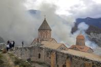 Armenians, one of them with an Armenian national flag, visit the 12th-13th century Orthodox Dadivank Monastery on the outskirts of Kalbajar, the separatist region of Nagorno-Karabakh, on Friday, Nov. 13, 2020. Under an agreement ending weeks of intense fighting over the Nagorno-Karabakh region, some Armenian-held territories, such as this area adjacent to the region, are passing to Azerbaijan. (AP Photo/Sergei Grits)