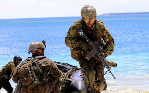 Japanese soldiers take part in joint military exercises between the US, Japan, France and UK on Naval Base Guam - Credit: AP