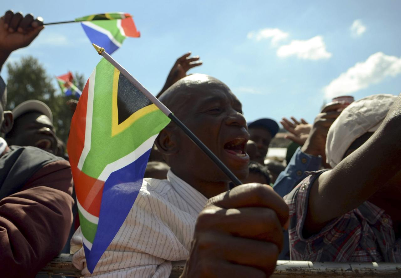 "A man cheers and waves a flag during Freedom Day celebrations at the Union Buildings in Pretoria, April 27, 2014. South Africa marked two decades of multi-racial democracy on Sunday, still feeling the loss of Nelson Mandela and in sombre mood just 10 days before elections which are expected to keep the African National Congress (ANC) party in power.Sunday's celebrations held a special poignancy as this is the first ""Freedom Day"" since the passing of Mandela, the anti-apartheid icon who died in December at the age of 95. REUTERS/Skyler Reid (SOUTH AFRICA - Tags: POLITICS ANNIVERSARY)"