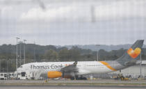 Seen through a perimeter fence, a Thomas Cook aircraft on the tarmac at Gatwick Airport, England, Monday, Sept. 23, 2019. British tour company Thomas Cook collapsed early Monday after failing to secure emergency funding, leaving tens of thousands of vacationers stranded abroad. (AP Photo/Alastair Grant)