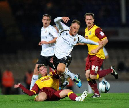 Port Vale's Sean Rigg tackled by Northampton Town's Ashley Corker