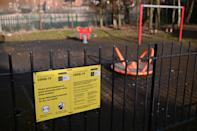 "<p>A Covid-19 information poster is pictured on the fence of an empty children's play park in Manchester, northern England, on February 15, 2021. - Britain intends to seek a ""cautious but irreversible"" ending of strict coronavirus restrictions, Prime Minister Boris Johnson said Monday as his government introduced hotel quarantine stays for arrivals from ""high risk"" nations. (Photo by Oli SCARFF / AFP) (Photo by OLI SCARFF/AFP via Getty Images)</p>"