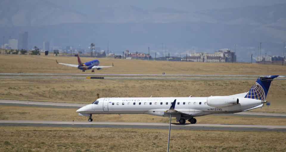 A United Express jet taxis down a runway as a Southwest Airlines plane takes off in the background at Denver International Airport, Tuesday, Aug. 24, 2021, in Denver. Two months after the Sept. 11, 2001 attacks, President George W. Bush signed legislation creating the Transportation Security Administration, a force of federal airport screeners that replaced the private companies that airlines were hiring to handle security. (AP Photo/David Zalubowski)