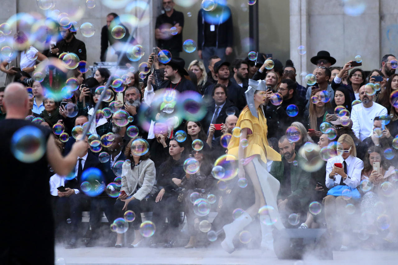 A show worker, left, produces bubbles as a model wears a creation as part of the Rick Owens Ready To Wear Spring-Summer 2020 collection, unveiled during the fashion week, in Paris, Thursday, Sept. 26, 2019. (AP Photo/Michel Euler)