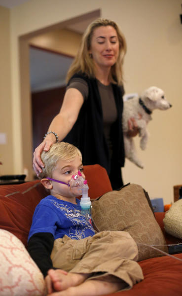In this Tuesday, Oct. 15, 2013 photo, Monique Howard holds Waldo as she caresses her son Carter's head while he sits through his asthma treatment at their Northbrook, Ill., home. On the days when asthma gives Carter the most trouble it reminds her about how doctors at Rush University Medical Center had to stop submitting applications for research grants to study childhood asthma and other diseases and disorders. Hospital officials have said the shutdown could have delayed funding for nearly half a year. (AP Photo/Charles Rex Arbogast)