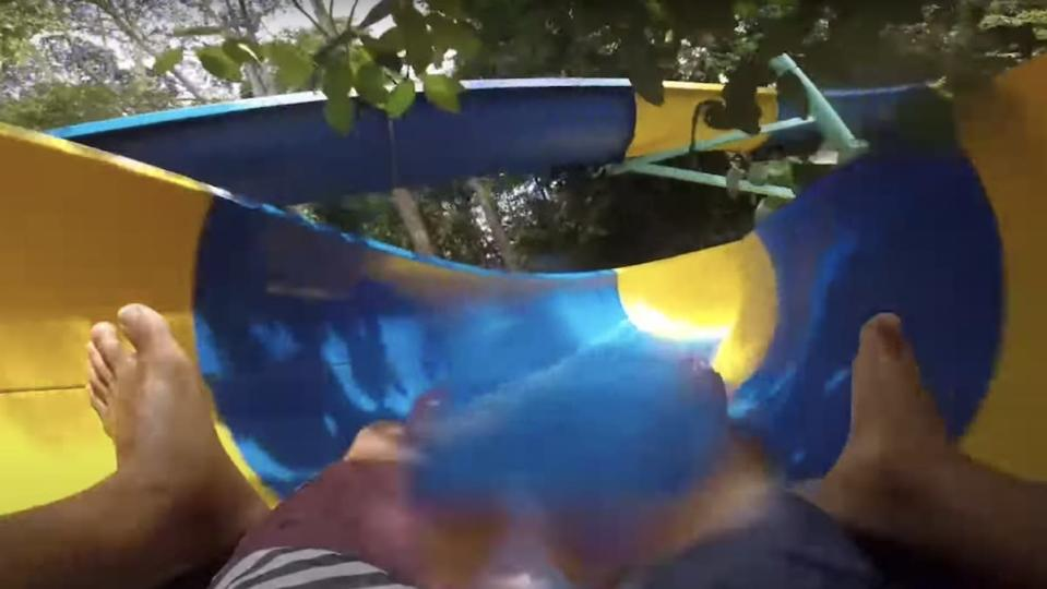 A first-person shot of two people on a mat going down a blue and yellow water slide