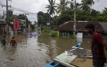 Sri Lankans stranded due to floods travel in a boat in an inundated street following heavy rainfall at Malwana, on the outskirts of Colombo, Sri Lanka, Saturday, June 5, 2021. Flash floods and mudslides triggered by heavy rains in Sri Lanka have killed at least four people and left seven missing, while more than 5,000 are displaced, officials said Saturday. Rains have been pounding six districts of the Indian Ocean island nation since Thursday night, and many houses, paddy fields and roads have been inundated, blocking traffic. (AP Photo/Eranga Jayawardena)