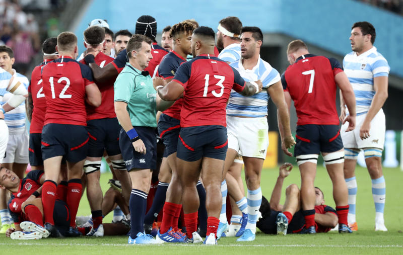 Referee Nigel Owens talks to England's Manu Tuilagi after a player scuffle during the Rugby World Cup Pool C game at Tokyo Stadium between England and Argentina in Tokyo, Japan, Saturday, Oct. 5, 2019. (AP Photo/Eugene Hoshiko)