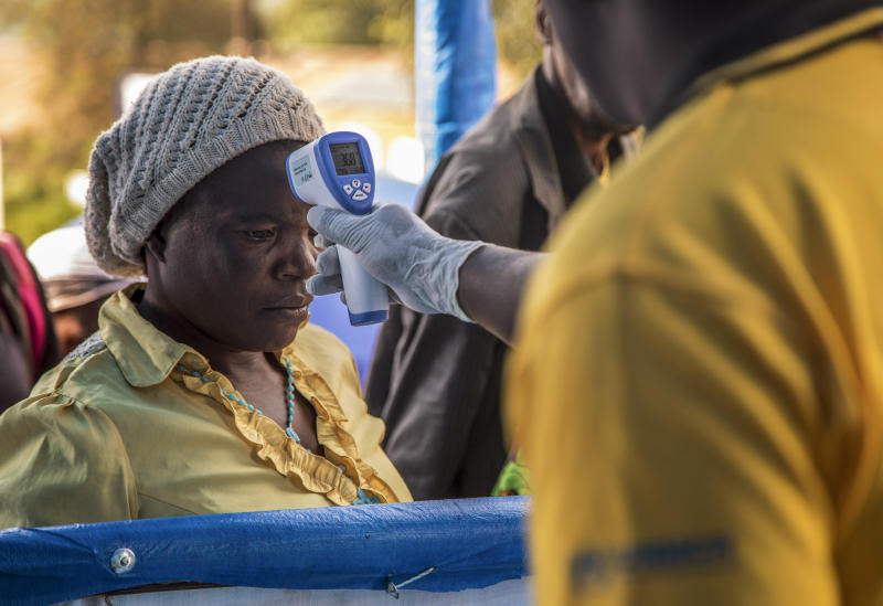 In this photo provided by the International Rescue Committee, a Congolese refugee is screened for Ebola symptoms at the IRC triage facility in the Kyaka II refugee settlement in Kyegegwa District in western Uganda, Thursday, June 13, 2019. The Congolese pastor who is thought to have caused the Ebola outbreak's spread into Uganda was unknown to health officials before he died of the disease, the World Health Organization's emergencies chief said Thursday, underlining the problems in tracking the virus. (Kellie Ryan/International Rescue Committee via AP)