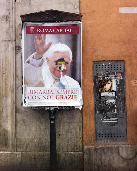 "This March 1, 2013 photo shows a billboard with a torn poster of Pope Benedict XVI, with writing reading in Italian ""You'll always be with us, Thank you"", in Rome. These are crazy days in Rome - where limbo reigns in parliament and papacy. Italy is usually a pretty anarchic place, with people bucking rules on everything from crossing the street to paying taxes. But the anarchy's going a bit far: Who's running the country? Who's running the church? Nobody really knows. (AP Photo/Joji Sakurai)"