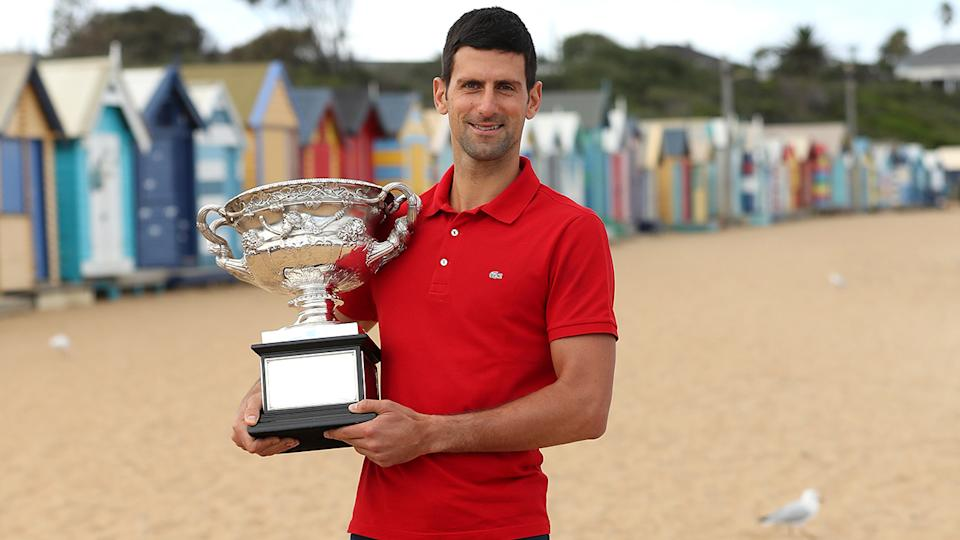 Novak Djokovic poses with the Norman Brookes Challenge Cup after winning the 2021 Australian Open Men's Final. (Photo by Graham Denholm/Getty Images)