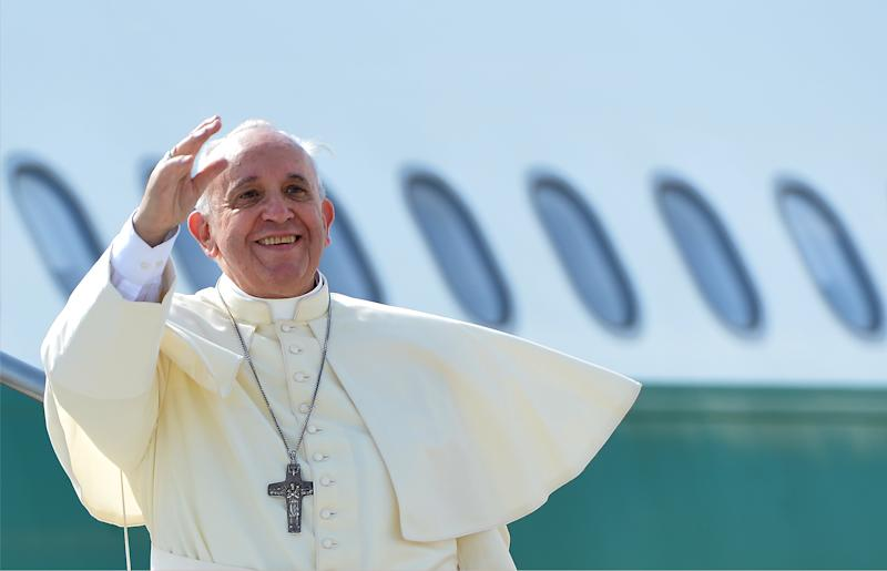 Pope Francis waves from the top of the stairs leading to the plane that will carry him to the South Korea, on August 13, 2014 at Rome's Fiumicino international airport