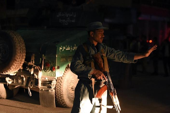 An Afghan policeman blocks a road near the Park Place guesthouse in Kabul on May 13, 2015 after gunmen stormed the place ahead of a planned concert (AFP Photo/Shah Marai)