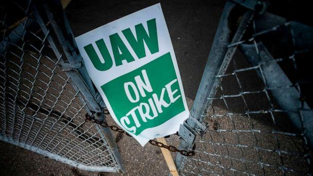 PHOTO: A United Auto Workers strike sign rests between the chains of a locked gate entrance outside of Flint Engine Operations in Flint, Mich., Sept. 16, 2019. (Jake May/The Flint Journal via AP, FILE)