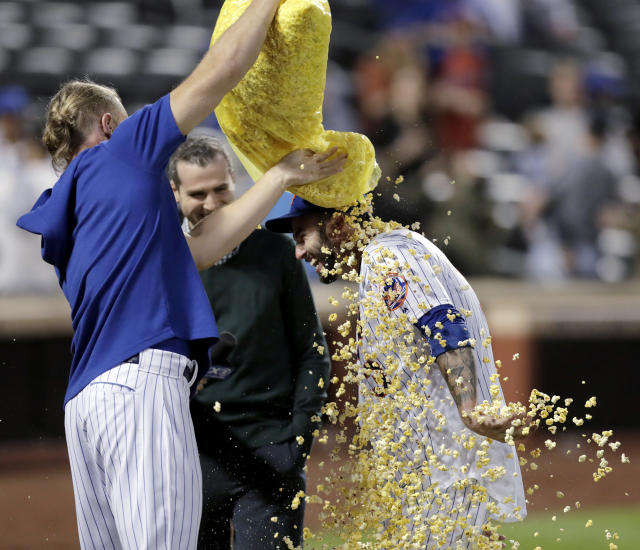 New York Mets starting pitcher Noah Syndergaard, left, showers Tomas Nido with popcorn after Nido hit a walk-off solo home run off Detroit Tigers relief pitcher Buck Farmer during the 13th inning of a baseball game Saturday, May 25, 2019, in New York. The Mets won 5-4. (AP Photo/Julio Cortez)