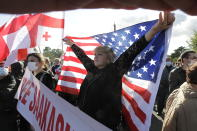 Georgian opposition supporters of former president Mikheil Saakashvili hold Georgian and American national flags during a rally in his support in front of the prison where former president is being held, in Rustavi, about 20 km from the capital Tbilisi, Georgia, Monday, Oct. 4, 2021. Saakashvili was detained in Tbilisi on Saturday, Oct. 1, 2021. Georgia earlier declared Saakashvili wanted as a person convicted in absentia in several criminal cases and treated as a suspect in some others. Georgian authorities have warned repeatedly that he would be detained immediately once over the border. (AP Photo/Shakh Aivazov)