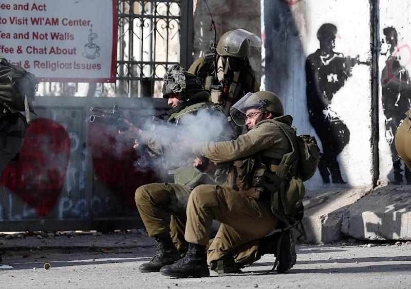 Israeli security forces fire teargas at Palestinians protesters in clashes at a controversial separation wall in the West Bank city of Bethlehem on December 18, 2015 (AFP Photo/Thomas Coex)
