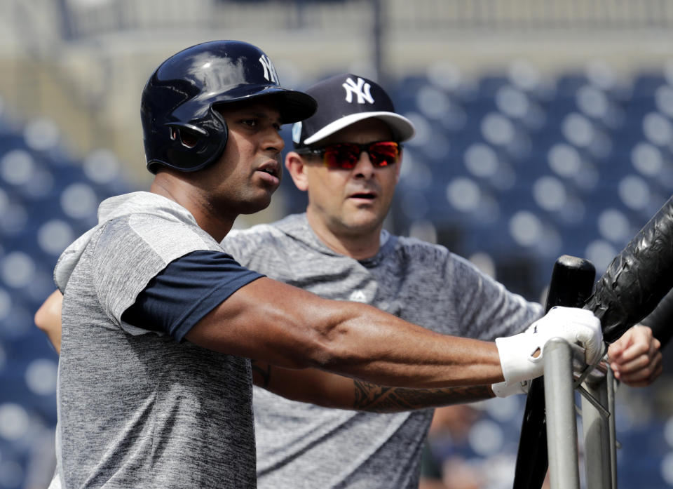 New York Yankees' Aaron Hicks, left, and manager Aaron Boone watch batting practice at the New York Yankees spring training baseball facility, Thursday, Feb. 21, 2019, in Tampa, Fla. (AP Photo/Lynne Sladky)