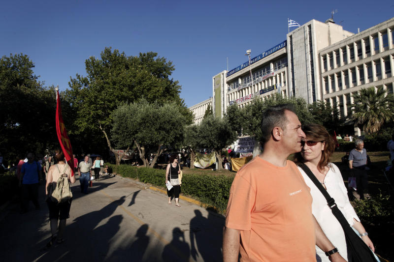 People walk past Greek state television ERT headquarters in Athens, on Wednesday, June 19, 2013. Fired ERT employees have continued unauthorized broadcasts since the broadcaster's June 11 closure, streamed mostly online and on disused analog frequencies. Greece's governing coalition parties met for a second time in three days to try and end a political crisis triggered by the closure of state broadcaster ERT.(AP Photo/Petros Giannakouris)