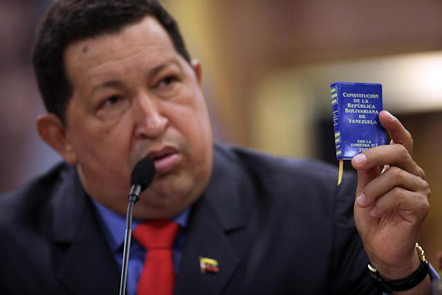 FILE - In this Oct 9, 2012 file photo, Venezuela's President Hugo Chavez holds a miniature copy of his country's constitution during a news conference in Caracas, Venezuela. The ailing president's health crisis has raised contentious questions ahead of the swearing-in set for Jan. 10, including whether the inauguration could legally be postponed. Officials have raised the possibility that Chavez might not be well enough to take the oath of office, without saying what will happen if he can't. The constitution says that if a president or president-elect dies or is declared unable to continue in office, presidential powers should be held temporarily by the president of the National Assembly and that a new presidential vote should be held within 30 days. (AP Photo/Rodrigo Abd, File)