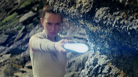 Actress Daisy Ridley as Star Wars character Rey holding a light blue lightsaber.