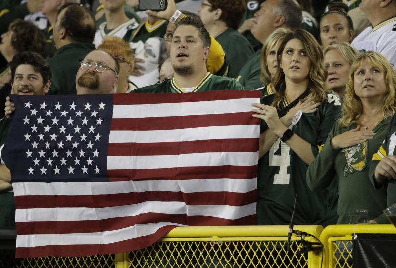 Fans in Green Bay stand to attention during the playing of the national anthem on Thursday. (AP)