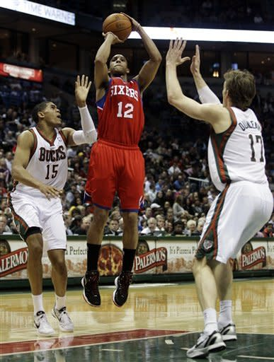 Philadelphia 76ers' Evan Turner (12) shoots between Milwaukee Bucks' Tobias Harris (15) and Mike Dunleavy (17) during the first half of an NBA basketball game, Wednesday, April 25, 2012, in Milwaukee. (AP Photo/Morry Gash)
