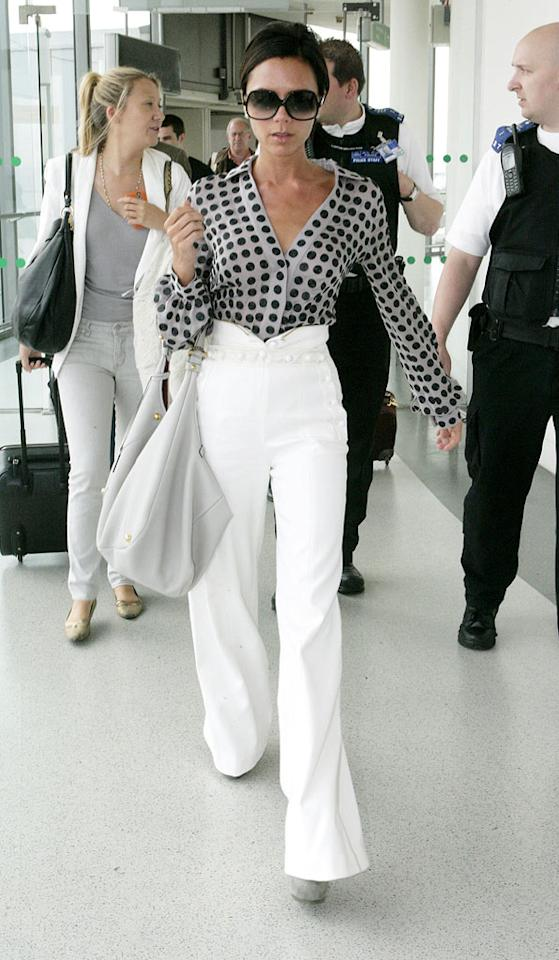 "She might not travel in the comfiest clothing, but Posh certainly looked stunning while sashaying through London's Heathrow Airport in a polka-dotted blouse, crisp high-waisted trousers, suede platform pumps, and her trademark shades. <a href=""http://www.infdaily.com"" target=""new"">INFDaily.com</a> - July 21, 2009"
