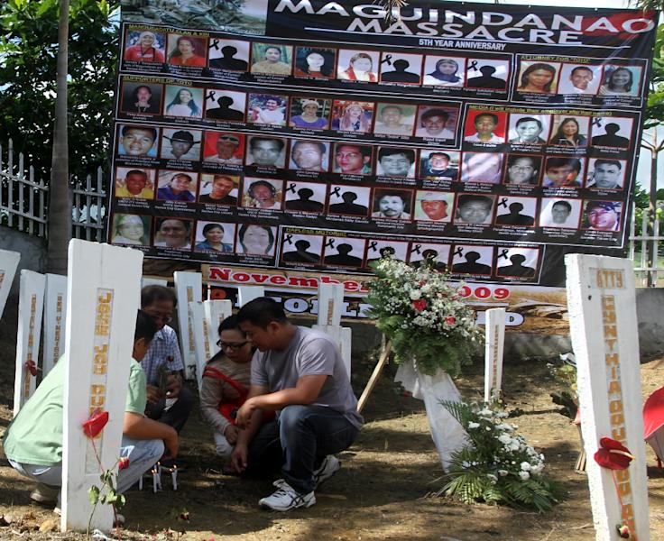 Relatives of the victims of the infamous Maguindanao massacre light candles on wood markers during the fifth year anniversary commemoration at the massacre site on November 23, 2014, in Ampatuan town, southern island of Mindanao (AFP Photo/Mark Navales)