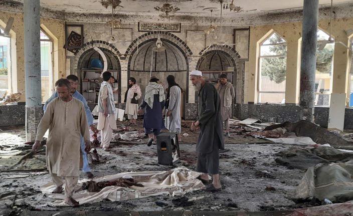 People view the damage inside of a mosque following a bombing in Kunduz, province northern Afghanistan, Friday, Oct. 8, 2021. A powerful explosion in the mosque frequented by a Muslim religious minority in northern Afghanistan on Friday has left several casualties, witnesses and the Taliban's spokesman said. (AP Photo/Abdullah Sahil)
