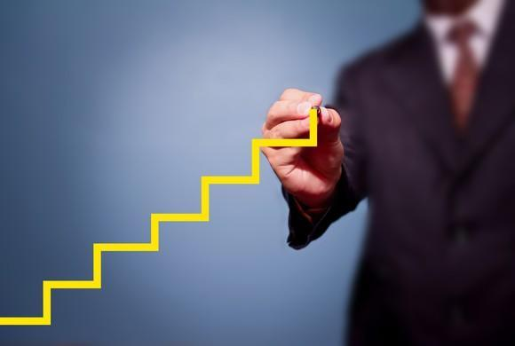 Man in a suit drawing a yellow step chart that's steadily climbing higher.
