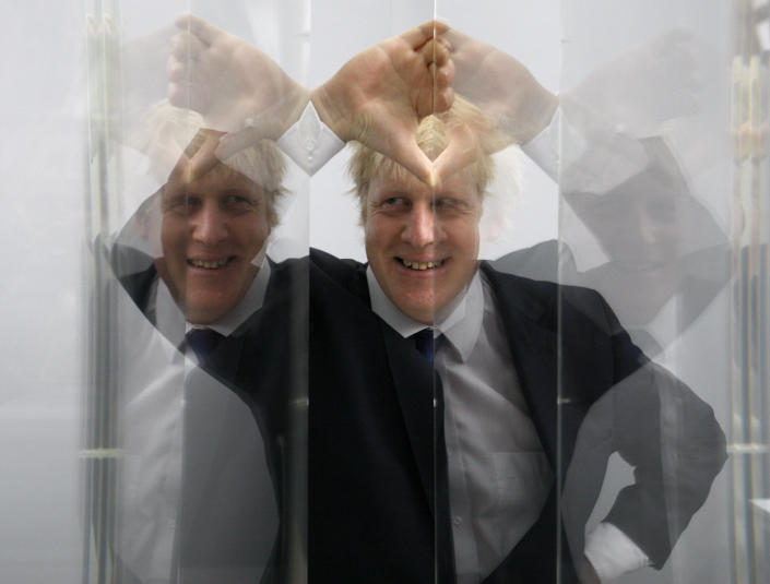 FILE - In this Friday, Jan. 14, 2011 file photo Boris Johnson, then Mayor of London in seen looking through perspex as models of the next two commissions that will appear on the fourth plinth in Trafalgar Square in London, are unveiled. (AP Photo/Kirsty Wigglesworth, File)