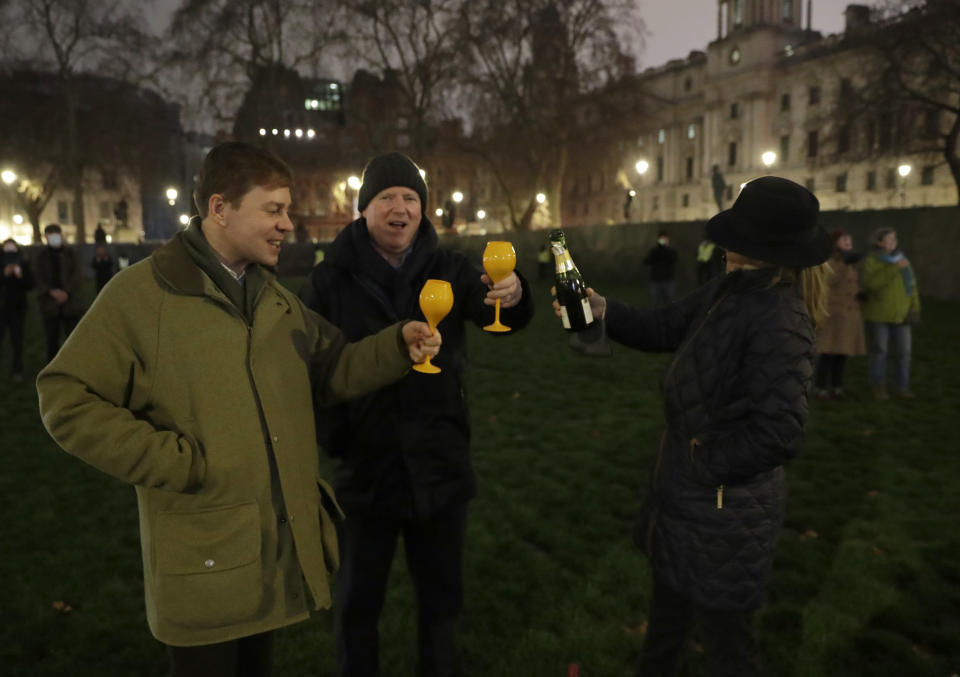 People raise a glass and celebrate in Parliament Square as the bell known as Big Ben strikes 2300, and Britain ends its transition period and formally leaves the European Union in London, Thursday, Dec. 31, 2020. Due to the coronavirus pandemic and the restrictions on gatherings people were moved on by police if they met in any number .(AP Photo/Matt Dunham)