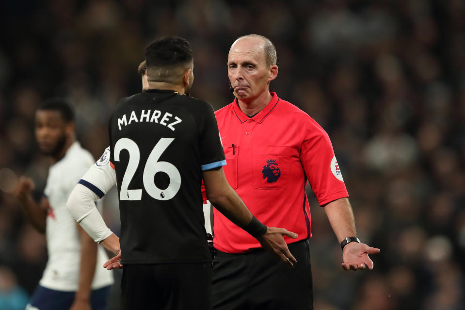 LONDON, ENGLAND - FEBRUARY 02: Match referee Mike Dean reacts to Riyad Mahrez of Manchester City during the Premier League match between Tottenham Hotspur and Manchester City at Tottenham Hotspur Stadium on February 2, 2020 in London, United Kingdom. (Photo by James Williamson - AMA/Getty Images)