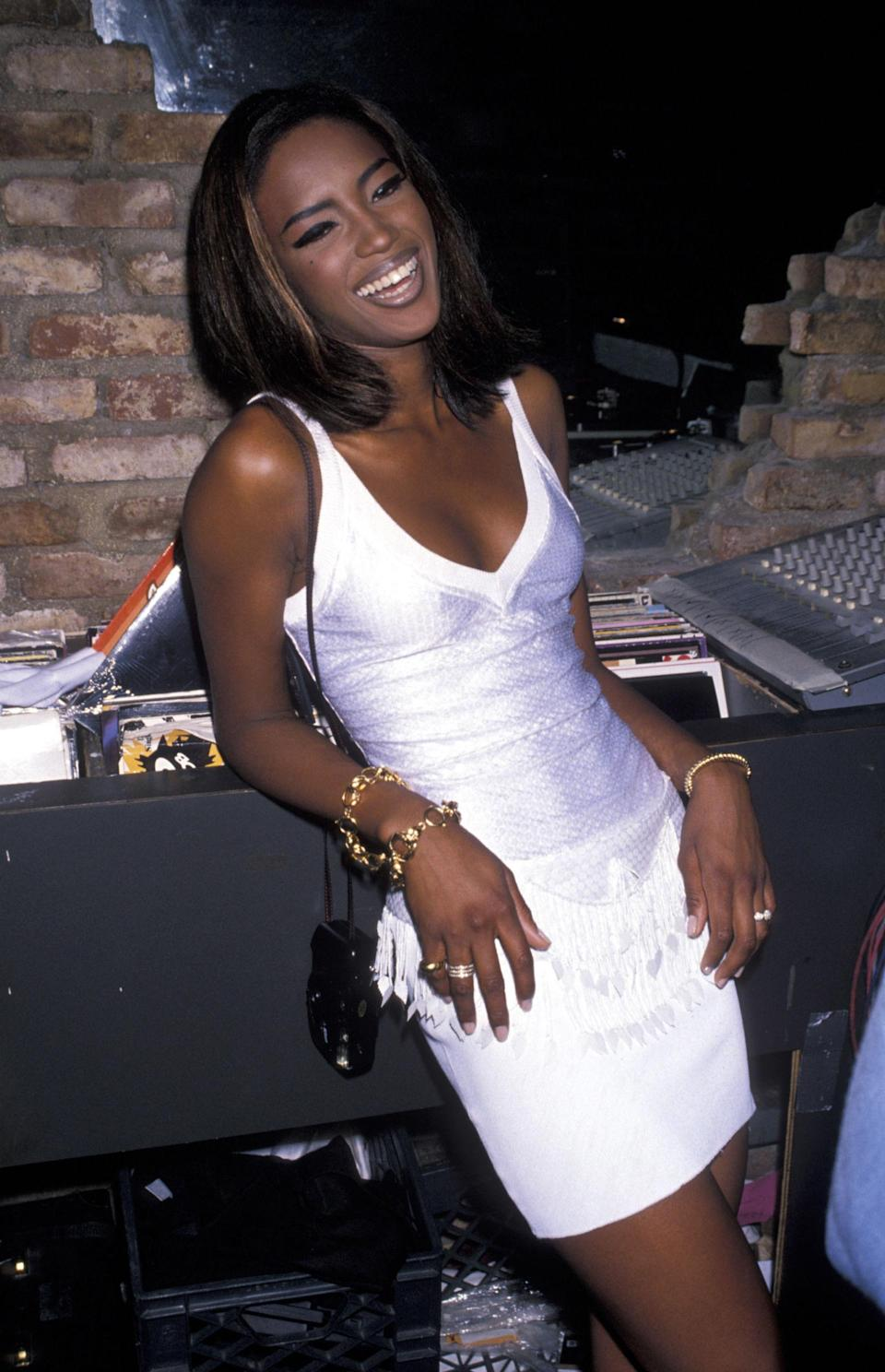 <p>Campbell chooses a simple white top and skirt for a party, 1990</p>