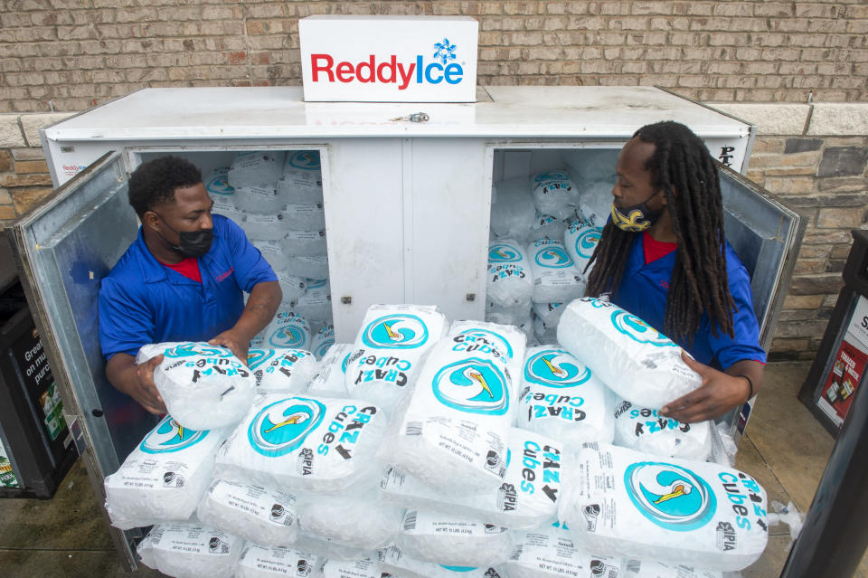 Corey Williams, right, and John Smith, both of Pelican Ice, hurriedly stack bags of ice into a gas station freezer in preparation for Tropical Storm Ida on Friday, Aug. 27, 2021 in Jefferson, La. Forecasters now say Ida could be a major Category 3 hurricane with top winds of 115 mph when it nears the U.S. coast. (Chris Granger/The Times-Picayune/The New Orleans Advocate via AP)