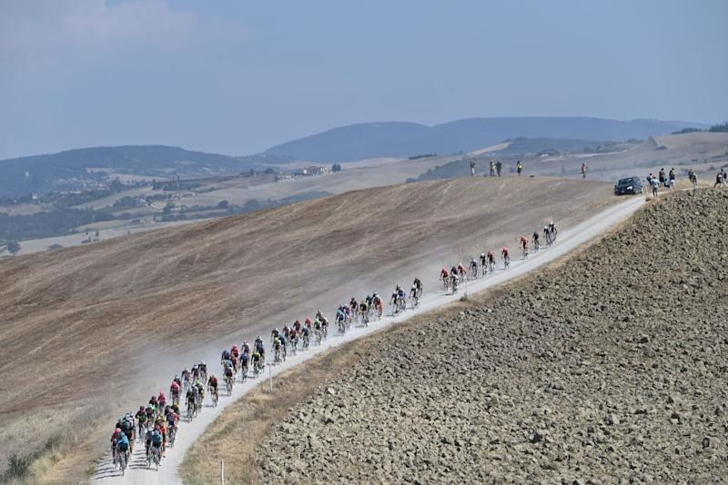 The pack of riders pedal through a dusty gravel road during the oneday classic cycling race Strade Bianche White Roads on August 1 2020 in Siena Tuscany Photo by Marco BERTORELLO AFP Photo by MARCO BERTORELLOAFP via Getty Images