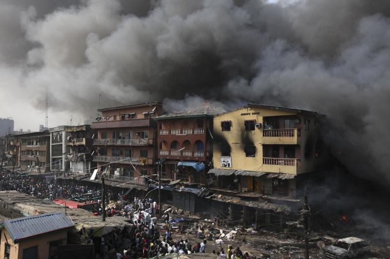 Residents look  as a fire burns out a residential homes and a warehouse on Lagos Island in Lagos, Nigeria, Wednesday, Dec. 26, 2012. An explosion ripped through a warehouse Wednesday where witnesses say fireworks were stored in Nigeria's largest city, sparking a fire. It wasn't immediately clear if anyone was injured in the blast that firefighters and locals struggled to contain. (Ap Photos/Sunday Alamba)