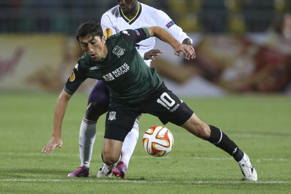 FILE - In this Oct. 2, 2014, file photo, Krasnodar's Odil Ahmedov, front, fights for the ball with Everton's Christian Atsu during the Europa League Group H soccer match between Krasnodar and Everton in Krasnodar, Russia. In a bid to complete the 2020 season in the midst of restrictions caused by the COVID-19 pandemic, the Chinese Football Association decided to split the 16 top-tier CSL teams into two groups based in the hub cities of Dalian and Suzhou. (AP Photo/Vitaly Timkiv, File)