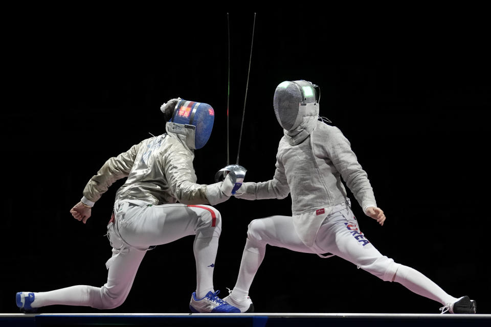 Enrico Berre of Italy, left, and Gu Bongil of South Korea compete in the men's Sabre team medal at the 2020 Summer Olympics, Wednesday, July 28, 2021, in Chiba, Japan. (AP Photo/Andrew Medichini)