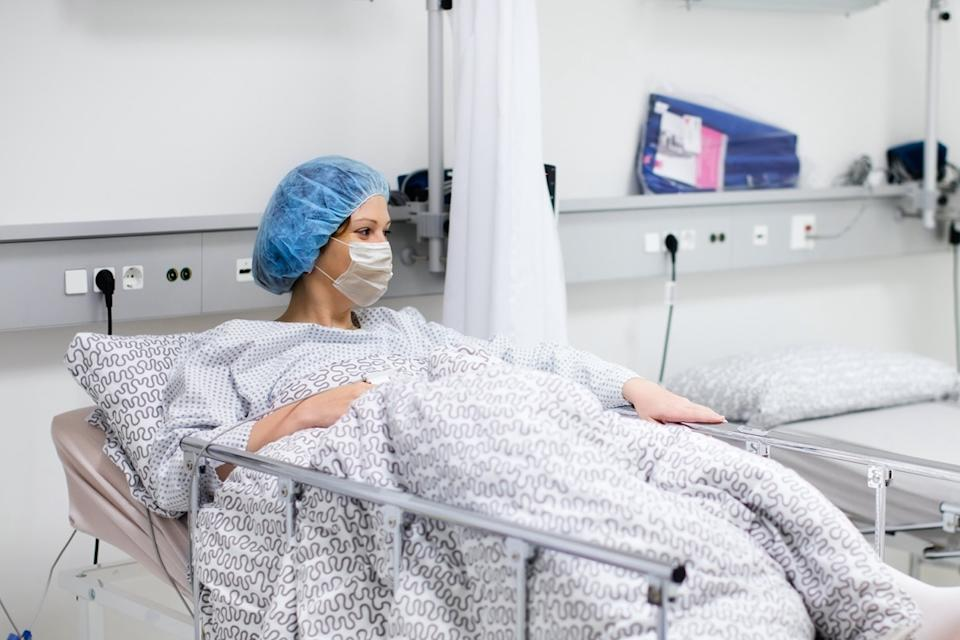Young woman wearing face mask in clinic ward recovering from coronavirus disease. Sick