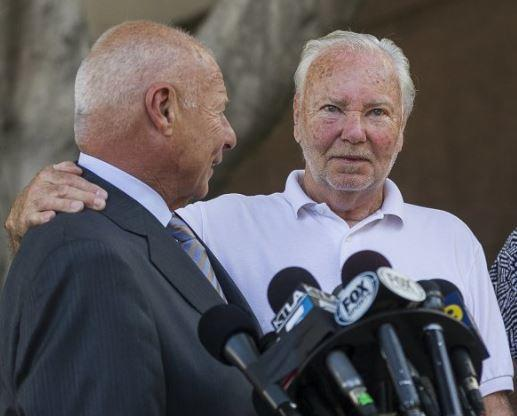 Two men embrace before a stand of microphones.