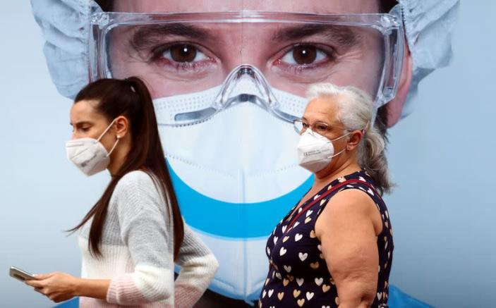 People, wearing protective face masks, walk past a dental clinic advertisement at Vallecas neighbourhood in Madrid