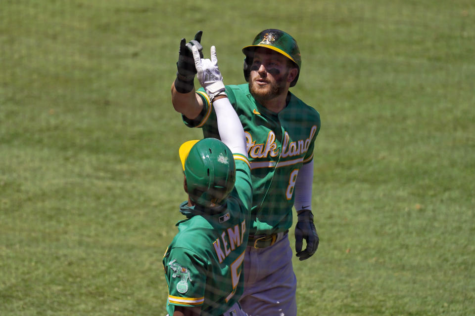 Oakland Athletics' Robbie Grossman, right, celebrates with Tony Kemp after hitting a two-run home run during the second inning of a baseball game against the Los Angeles Angels Wednesday, Aug. 12, 2020, in Anaheim, Calif. (AP Photo/Mark J. Terrill)