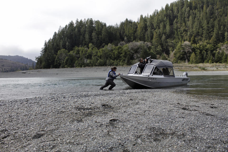 FILE - In this March 5, 2020, file photo, Hunter Maltz, a fish technician for the Yurok tribe, pushes a jet boat into the low water of the Klamath River at the confluence of the Klamath River and Blue Creek as Keith Parker, as a Yurok tribal fisheries biologist, watches near Klamath, Calif., in Humboldt County. Federal officials announced Wednesday that farmers who rely on a massive irrigation project spanning the Oregon-California border will get 8% of the deliveries they need amid a severe drought. (AP Photo/Gillian Flaccus, File)