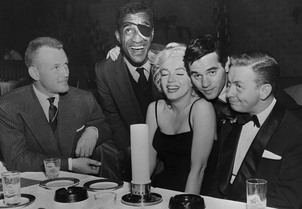 <p>Marilyn Monroe laughing it up with Jacques Sernas, Sammy Davis, Jr, photographer Milton H Greene, and jazz musician Mel Torme at Crescendo night club on the Sunset Strip in 1960.</p>