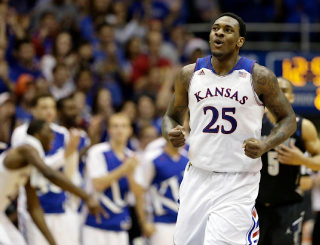 Kansas' Tarik Black(25) celebrates after a teammate made a shot during the second half of an NCAA college basketball game against Georgetown Saturday, Dec. 21, 2013, in Lawrence, Kan. Kansas won the game 86-64. (AP Photo/Charlie Riedel)