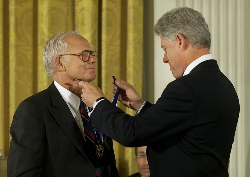 FILE - In this Aug. 9, 2000, file photo President Clinton, right, awards the Presidential Medal of Freedom to Jim Burke, CEO of Johnson and Johnson, during ceremonies in the East Room of the White House in Washington. When seven people died in 1982 after taking Tylenol capsules tainted with cyanide, Johnson & Johnson Chairman Jim Burke ordered a recall of millions of bottles of the drug. In 1986, after another death, Burke pulled his company's over-the-counter capsules off the market permanently. Burke's response is widely considered a standard of responsibility other businesses should strive for.(AP Photo/Pablo Martinez Monsivais, File)