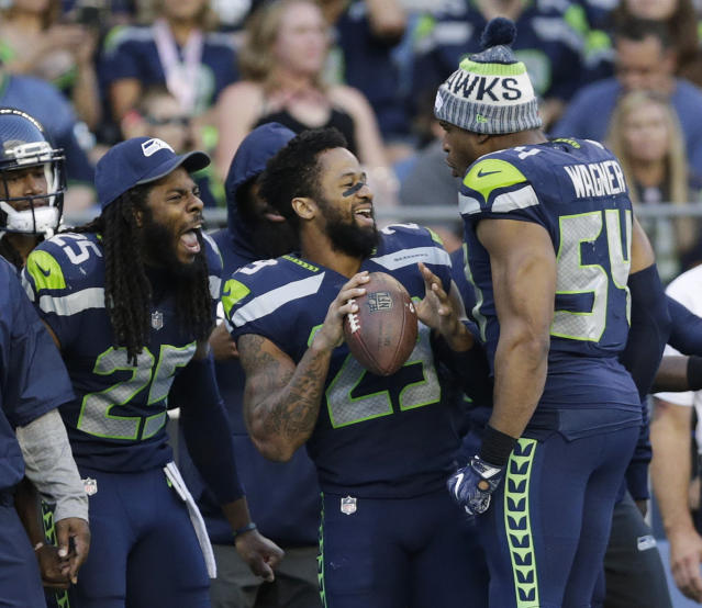 FILE - In this Aug. 25, 2017, file photo, Seattle Seahawks cornerback Richard Sherman, free safety Earl Thomas, center, and middle linebacker Bobby Wagner (54) react on the sideline during the second half of an NFL football preseason game against the Kansas City Chiefs, in Seattle. Thomas is putting the pressure on the Seattle Seahawks for a new contract, saying he will not participate in any team activities until his contract situation is resolved. That includes the upcoming mandatory minicamp. (AP Photo/John Froschauer, File)