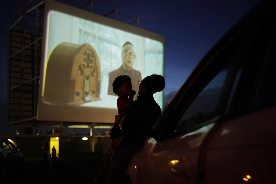People watch from their car during a drive-in screening of documentaries on Tulsa, Okla., during centennial commemorations of the Tulsa Race Massacre, Wednesday, May 26, 2021, in Tulsa, Okla. (AP Photo/John Locher)